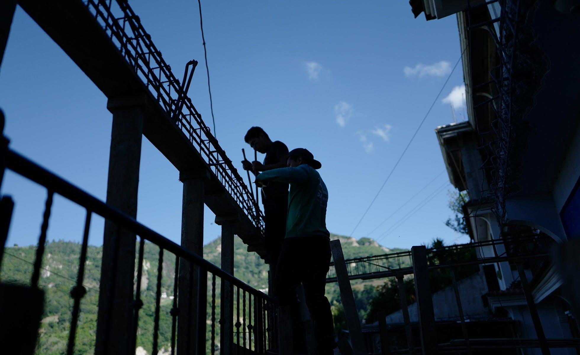 Después de estar deportado, Janio (en la parte superior de la imagen) regresó a trabajar en la construcción con su padre. Tiene que ganar dinero para pagar la deuda que contrajo para hacer su viaje a EU. Foto Morena Pérez Joachin.