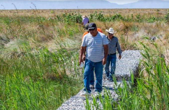 Ejidatarios caminan sobre una presa de gaviones que ha quedado en el desierto y sin agua.