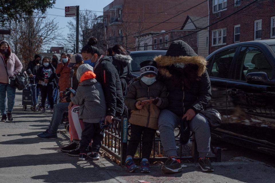 Familias esperan en línea para registrarse y recoger alimentos en Corona, Queens.